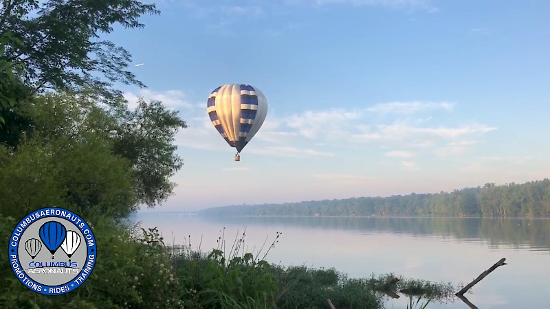 Balloon flight over water where photo is taken from ground level looking up at a beautiful sky.